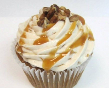 spiced caramel apple cupcake drizzled with caramel and topped with pecans