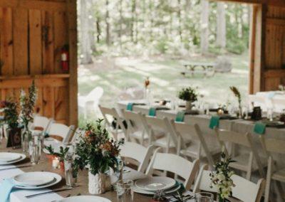 Boho wedding reception table settings in barn