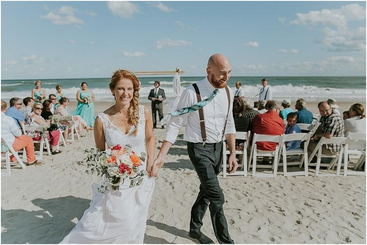 Boho beach wedding bride and groom with floral accents