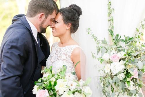 Boho bride aand groom posing near white-washed barn in Chapel Hill